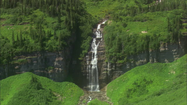 ws waterfall over cliff in green, partly forested mountain landscape / glacier national park, montana, usa - glacier national park us stock videos and b-roll footage