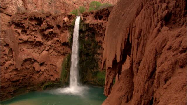 vidéos et rushes de a waterfall plunges over a cliff into a pool. - chute d'eau