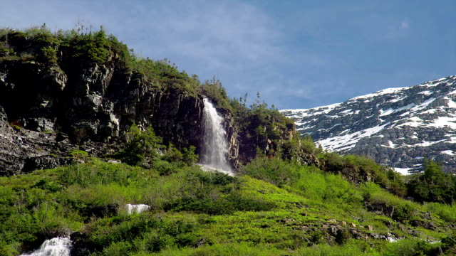 a waterfall pours off a cliff. - glacier nationalpark stock-videos und b-roll-filmmaterial