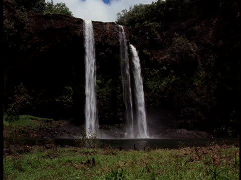 a waterfall splashes down a rocky cliff. - cloud computing stock videos & royalty-free footage