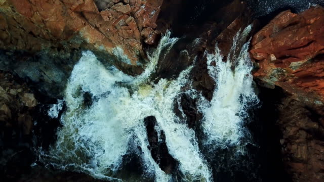 Waterfall surrounded by rocks. Aerial view