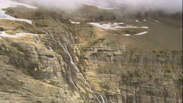 a waterfall tumbles down a mountainside in glacier national park, montana. available in hd. - glacier national park us stock videos and b-roll footage