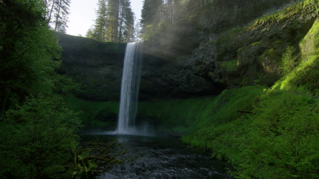 LOW ANGLE WIDE SHOT waterfall with mist and sun rays in lush green forest