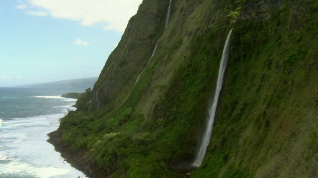 Waterfalls spill down the side of steep seacliffs on Hawaii's scenic Hamakua Coast.