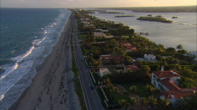 LOW AERIAL Waterfront homes and beach at Palm Beach, Florida, USA
