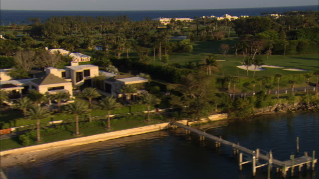 LOW AERIAL Waterfront homes and golf course at Palm Beach, Florida, USA