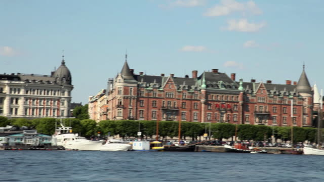POV WS Waterfront houses of old town with sailboats moored by embankment / Stockholm, Sweden