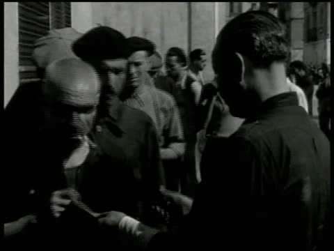 vídeos de stock e filmes b-roll de waterfront residential buildings. vs dock workers in breadline. men taking bread handed to them. three children led from building by auxilio social... - 1940