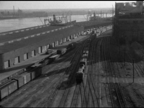 vídeos y material grabado en eventos de stock de waterfront storage warehouse buildings rail yard w/ train locomotive commercial boxcars moving slowly down inside railroad track note some spots... - c119gs