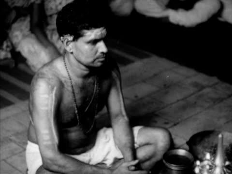 VS Brahmin Pandit Rama Shastri at ceremony for friend praying flowers almost covering Hindu deity painting priest w/ flames offerings CU Brahmin...