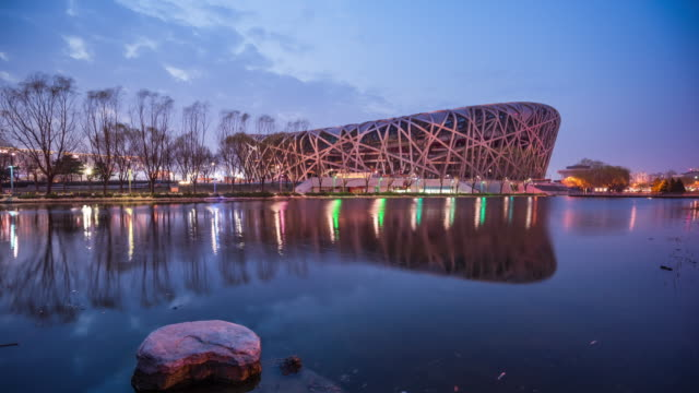 waterfront view of modern stadium dusk to night transition - beijing stock videos & royalty-free footage