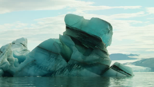 waterlevel track round large coloured iceberg with glacier in background - スヴァールバル諸島およびヤンマイエン島点の映像素材/bロール