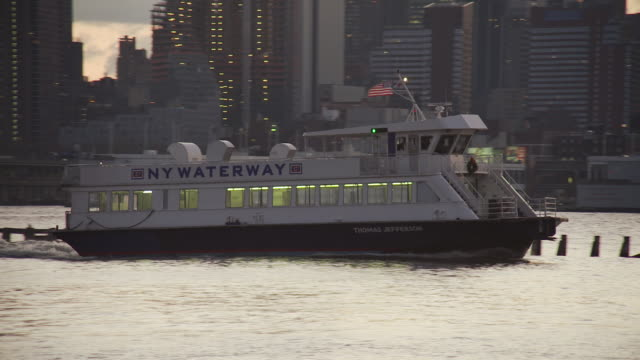 ny waterway ferry on the hudson river turns and sets a course for manhattan with birds flying and the skyscrapers of new york city in the background - lettera maiuscola video stock e b–roll