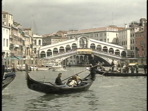 waterways in venice there is an dissolve opening long shot of gondola boats floating in a waterway there is a bridge in the background with buildings... - sport video stock e b–roll
