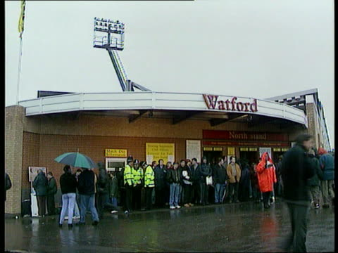 b1645 england herts watford vicarage road fans outside vicarage road stadium in rain herts cms official with megaphone - 水の形態点の映像素材/bロール