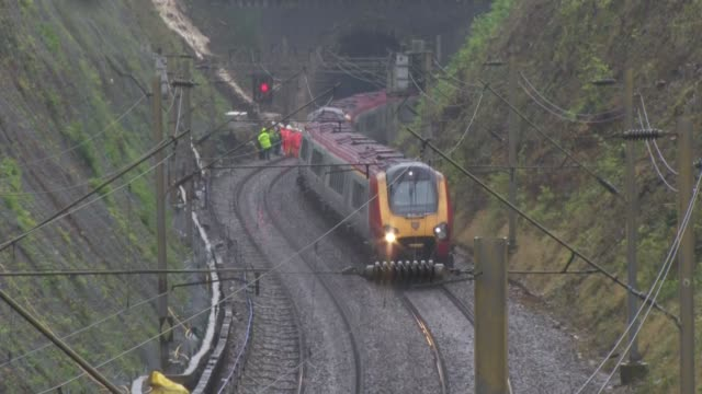 watford train derailment scene; england: hertfordshire: watford: ext / rain workers along train tracks near tunnel entrance where landslip caused... - 脱線点の映像素材/bロール
