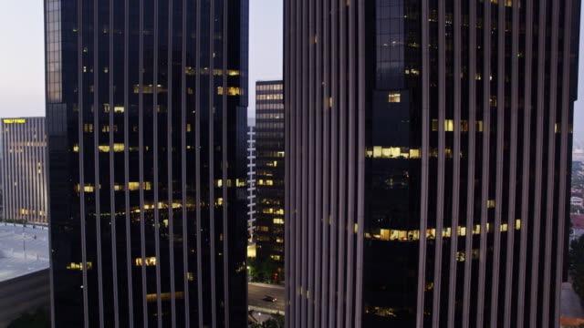 watt plaza towers lighting up in century city, los angeles - drone shot - century city stock-videos und b-roll-filmmaterial