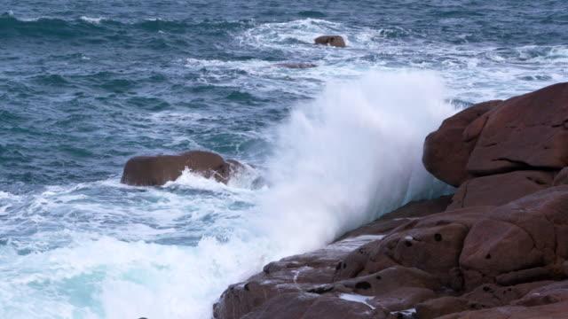 wave breaking on rocks at pink granite coast near ploumanach. - bretagna video stock e b–roll