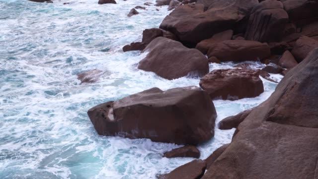 Wave breaking on rocks at pink Granite Coast near Ploumanach.