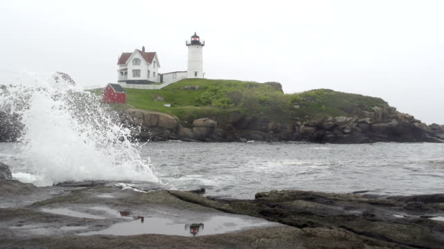 wave breaking over rocky shoreline with lighthouse in distance - maine stock videos & royalty-free footage