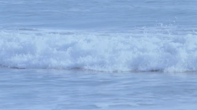 a wave breaks into foam in the ocean. - tide stock videos & royalty-free footage