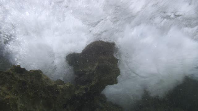 wave crashes into rock pool on beach, bahamas - bimini stock videos & royalty-free footage