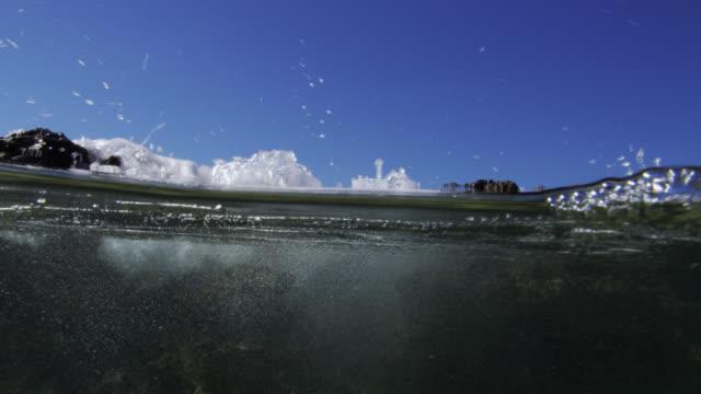 stockvideo's en b-roll-footage met wave crashes into rock pool on beach, bahamas - bimini