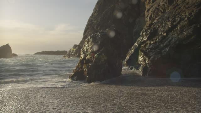 Wave crashes over big rock on coast