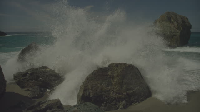 Wave crashes over rocks on beach