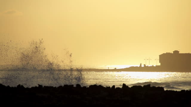 wave hitting rocks at sunrise - mgost stock videos and b-roll footage