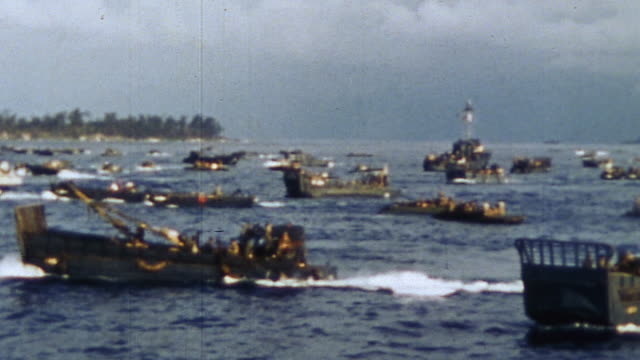 WS Wave of LCVP landing crafts carrying US Marines approaching Orange Beach during WWII / Peleliu Palau