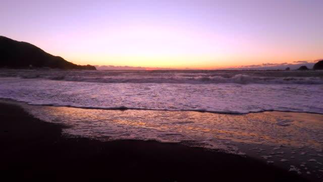 vídeos de stock, filmes e b-roll de onda na praia ao pôr do sol - 4 k - plusphoto