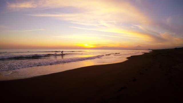 vídeos de stock, filmes e b-roll de onda na praia ao pôr do sol -surfing- 4 k - plusphoto