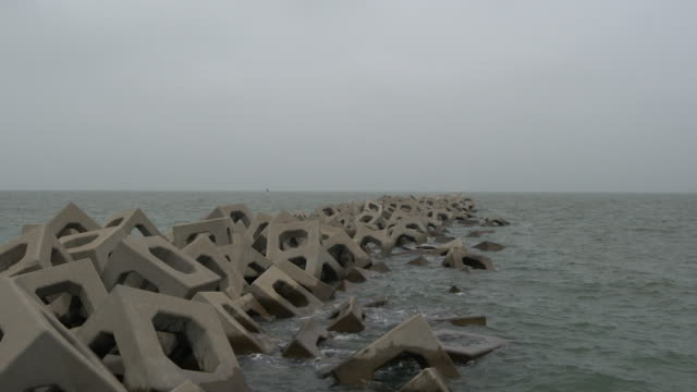 wave patting on jetty under overcast sky - jetty stock videos & royalty-free footage