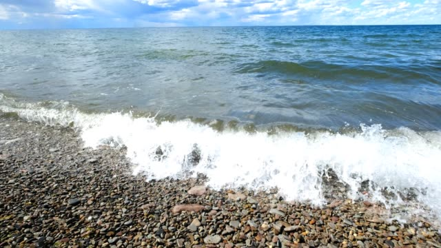 wave rolling in wide beach with stone in summer in daylight - riva dell'acqua video stock e b–roll