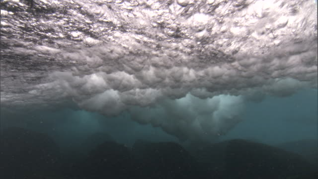 wave rolls in over rocky shallows, galapagos islands - audio available stock videos & royalty-free footage
