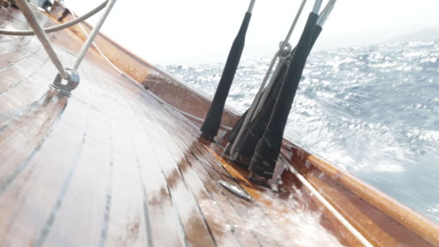 cu wave splashing over wooden deck of yacht  in rough sea - wet stock videos & royalty-free footage