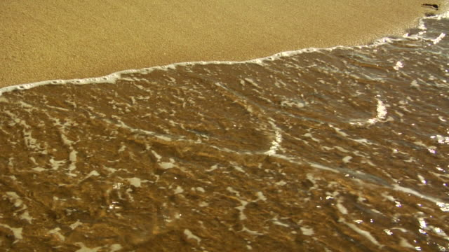 CU, Wave washing over footprints on beach, Provincetown, Massachusetts, USA