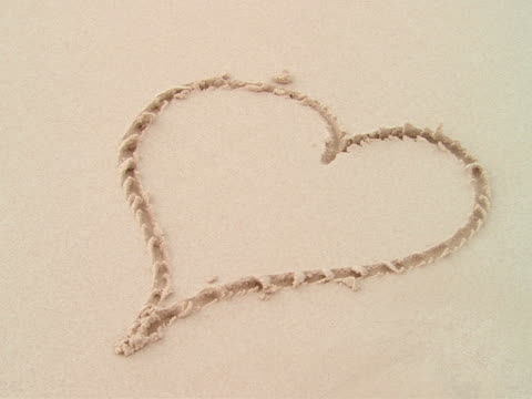 CU,  wave washing over heart shape drawn in sand,  Harbour Island,  Bahamas