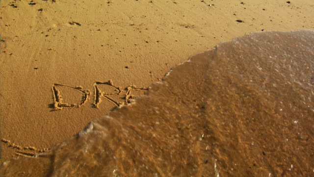 "CU, Wave washing over word ""dreams"" written in sand, Provincetown, Massachusetts, USA"