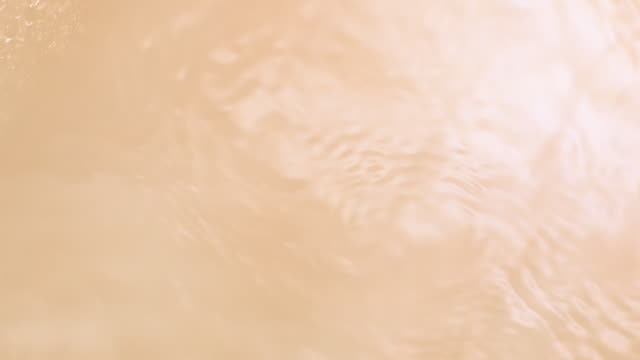 waves and ripples on water surface from above in beige color background - shaking stock-videos und b-roll-filmmaterial