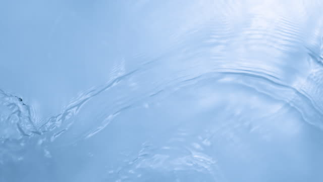 stockvideo's en b-roll-footage met waves and ripples on water surface overhead in pastel blue color background - swirl pattern