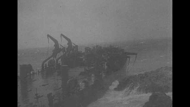 stockvideo's en b-roll-footage met waves batter large ship against rocks / men on ship stand around ring as it moves across deck in storm, two men either jump or fall off / us soldiers... - scheepswrak