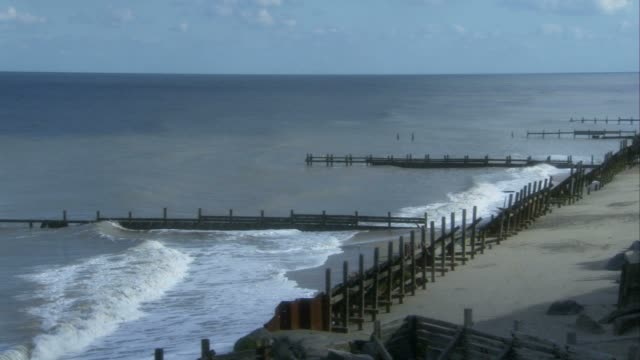 waves beat against coastal defenses in happisburgh, england. available in hd. - 浸食された点の映像素材/bロール