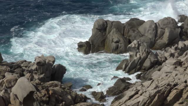 waves beating granite rocks on capo testa - sardinia stock videos & royalty-free footage