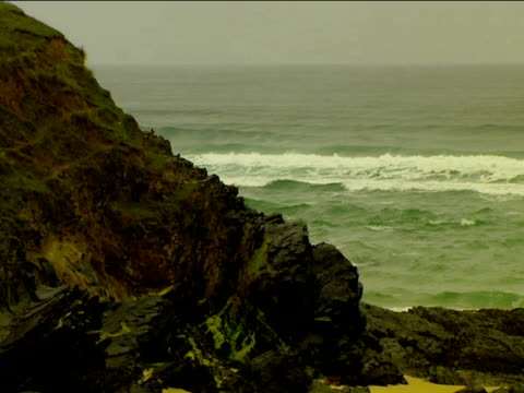 Waves break against sandy beach and rocks