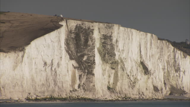 waves break against the white cliffs of dover. - dover kent stock-videos und b-roll-filmmaterial