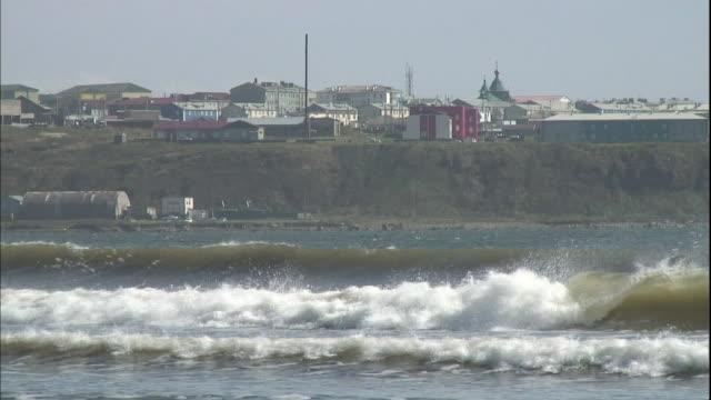 waves break along a shorelines near a hilltop kunashiri island village. - tornspira bildbanksvideor och videomaterial från bakom kulisserna