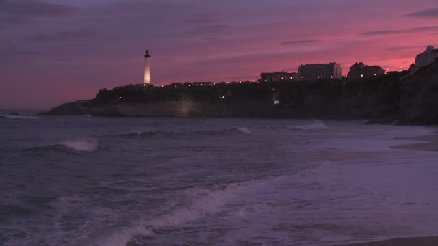 Waves break along the seafront in Biarritz, France at sunset.