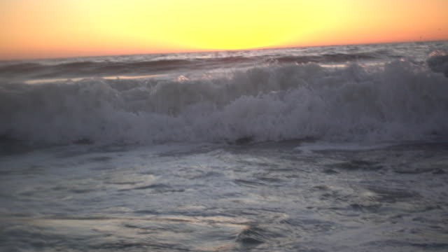 waves break in the pacific ocean at sunset. - slow motion - フェードアウト点の映像素材/bロール